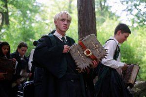Malefoy tenant son Monstrueux Livre des Monstres dans PA/f